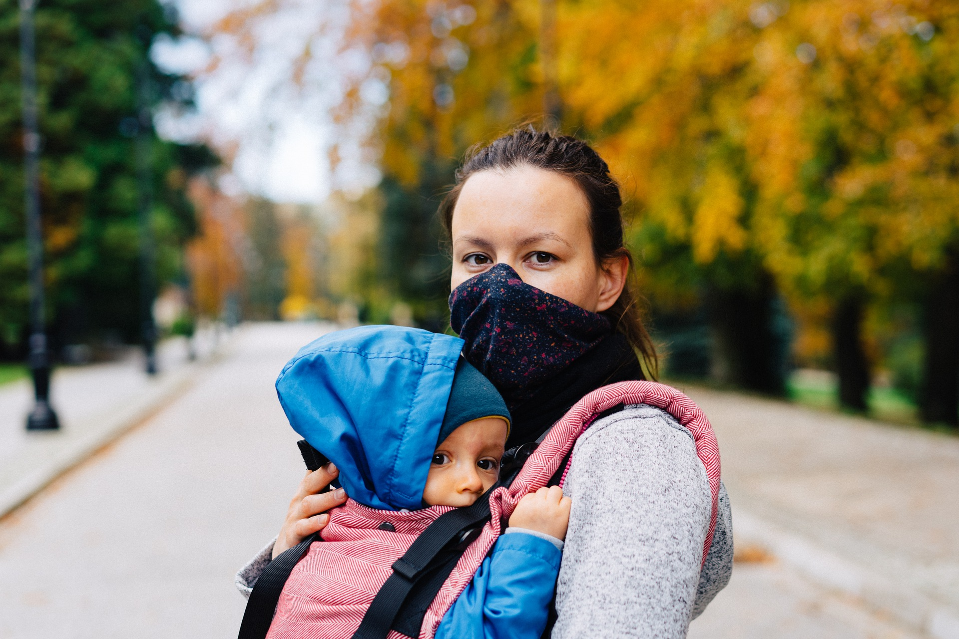 Woman wearing COVID-19 mask and holding a baby.